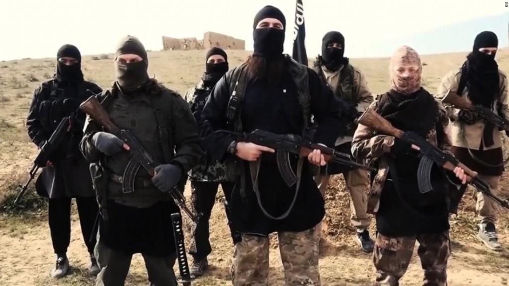 Hayat Boumedienne aurait été identifiée ici, en treillis, arme à la main, sur la gauche de l'homme prenant la parole. (Capture d'écran de la vidéo de l'Etat islamique)